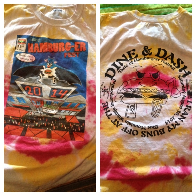 "Tie dye! The front has a fake comic book cover (the festival's theme was Superheroes) with the Hamburg movie theater showing ""The Dark Cow Rises."" The back has the race logo, a determined-looking running hamburger."